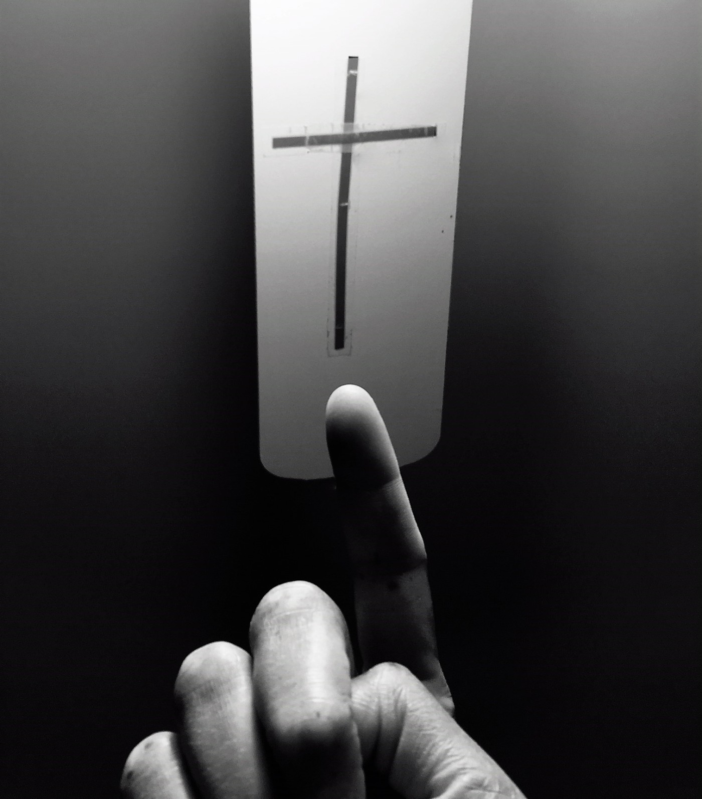 finger pointing to a cross